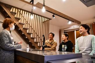 設計を手掛けた芳賀光さんの新居で、一家とだんらんする坪谷和彦さん(右)