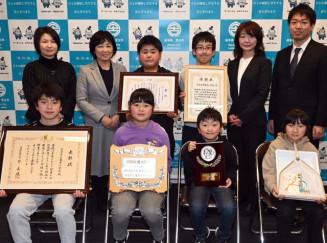 自然保護活動に関して受けた三つの表彰状などを掲げる亀岳小の児童と教職員