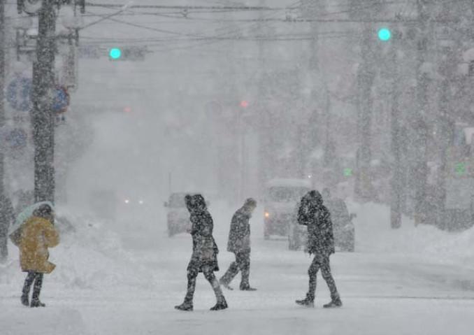 雪が激しく降る中、道路を横断する人たち=29日午前11時15分、盛岡市菜園