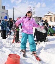 昔ながらのスキーを履き、笑顔で滑る子どもたち
