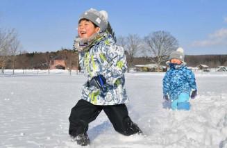 青空の下、雪上を駆け回る子どもたち