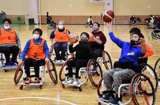 車いすバスケットボールでシュートを放つ練習に熱が入る参加者。会場は終始笑顔があふれた