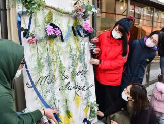 仲見世通りに出現したつり看板。三浦綾さん(右手前)と佐々木江利さん(左から2人目)が制作した