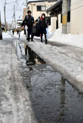 雪解けで水たまりができ、足元を気にしながら歩く中学生たち。盛岡市内の生活道は除雪が思うように進んでいない=2日、同市下ノ橋町
