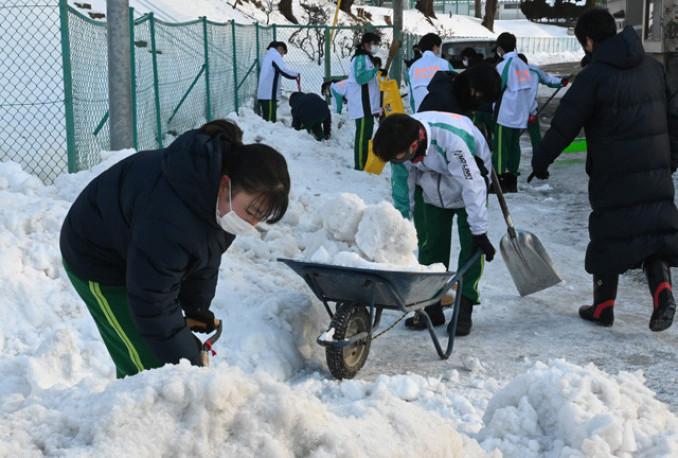 固まった雪に苦戦しながらも、作業に汗を流す河南中の生徒たち