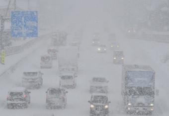 吹雪で視界が利かず、ライトをつけて走る車両=4日午後0時55分、盛岡市山王町・国道4号