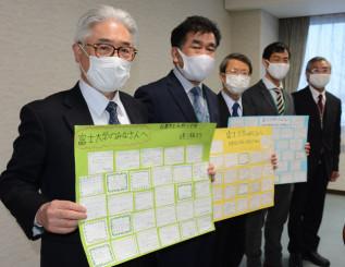 南城小児童のメッセージカードを掲げる(左から)岡田秀二学長、高橋彰校長ら
