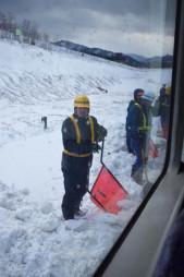 動けなくなった列車と線路の間で固まった雪をかき出す作業員=5日午後1時55分、遠野市綾織町