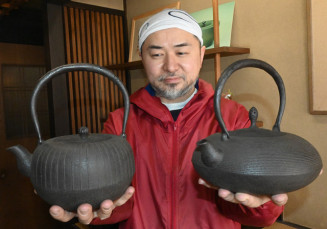 鈴木盛久工房が出した縦筋紋平丸形鉄瓶(左)と糸目紋布団形鉄瓶を持つ鈴木成朗社長