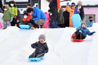 市内各地から雪を集めて作った雪山で、思い思いにそり遊びを楽しむ子どもたち