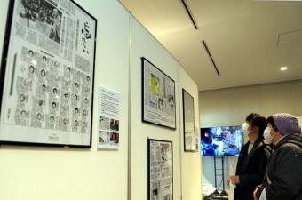 岩手日報社の特集紙面など紹介するコーナーで、震災直後の紙面に見入る来場者