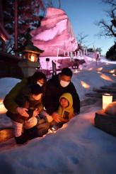 キャンドルの明かりを見つめる親子。奥はライトアップでカラフルに彩られた烏帽子(えぼし)岩=12日、盛岡市内丸・桜山神社