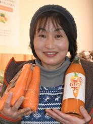 「大地の雫」と原料のニンジンを手に「奥玉の大地が育んだ味」と語る小野寺奈津子さん