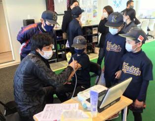 盛岡市のスポ少の選手を検診する品川清嗣医師(左)。年に1回の定期検診で大きなけがを予防できる