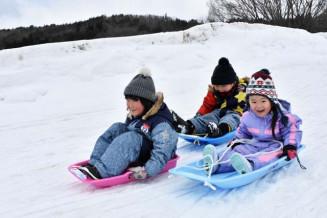 歓声を上げながら雪の巨大滑り台を楽しむ子どもたち