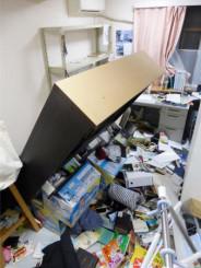 地震ため家具が倒れ、家財が散乱した民家の部屋=福島県郡山市