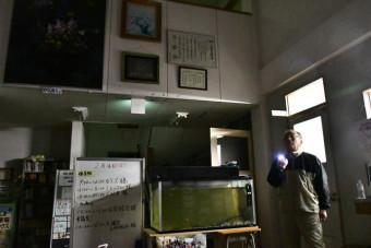 地震による停電で照明が落ち、非常用電灯や懐中電灯で対応する一関市の狐禅寺市民センター職員=14日午前0時10分