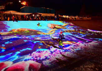 雪上に映し出された海の世界で、そり遊びを楽しむ子どもたち=13日、八幡平市・安比高原スキー場