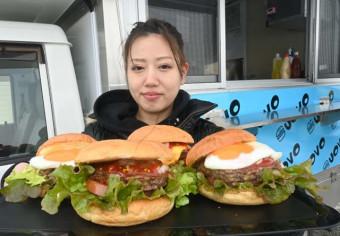キッチンカーの前でハンバーガーをPRする吉田葉月さん