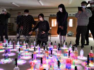 製作したペットボトル灯籠を見つめる南区の住民