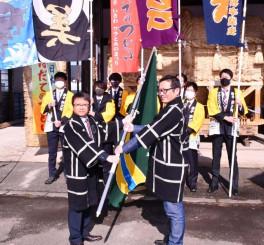 千田達志さん(左)から厄年連旗を受け取る小野寺誠さん