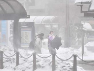 吹雪で視界が利かない中、目的地へ向かう人たち=16日午前10時38分、盛岡市盛岡駅前通