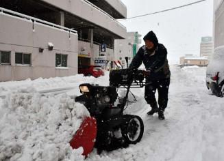 ビル周辺の歩道に積もった雪をかき出す男性=17日午前9時54分、北上市大通り