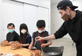 手作りの型に金属が流し込まれる瞬間を見つめる児童