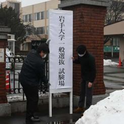 2次試験に向け、看板を設置する岩手大の職員=盛岡市上田
