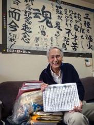 書き続けてきた手記を持つ久保秋悦さん。自宅の壁には2015年の入居時に書いた決意文が飾られている。久保さんの左は書きためた手記のファイル=釜石市上中島町