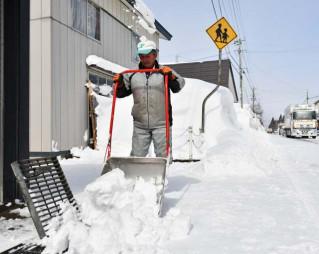 自宅に積もった雪を流雪溝に運ぶ男性=25日午前10時52分、西和賀町沢内新町