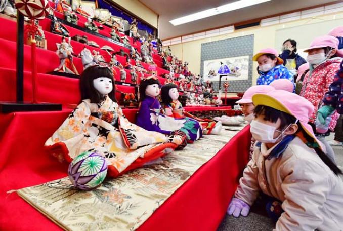 ひな壇に飾られた人形を眺める園児たち=26日、遠野市新町・臼井金物店器のうすい