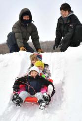 高さ5メートルの山からのそり滑りを楽しむ子どもたち