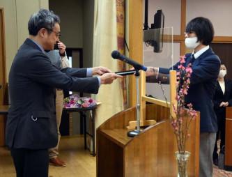 高畑嗣人教育長から修了証書を受け取る亀山大起さん(右)
