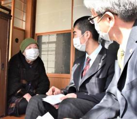 「元気に頑張って」。佐々木道さん(左)から励ましの言葉を受ける佐々木ヒロさん(中央)と村上弘校長