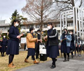 卒業式を終え、モニュメント「新しい世界へ」をくぐる卒業生=二戸市・福岡高
