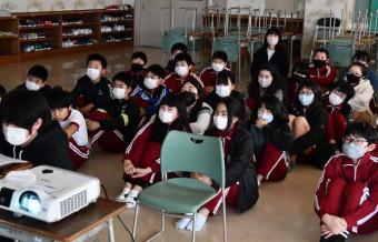 プロジェクターで映し出された被災地の様子を見ながら、千田剛校長の話を聞く湯本小の6年生
