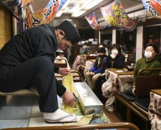こたつ列車内で熟練の技を披露する四作雄治さん(左)