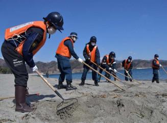 砂をかき分け、行方不明者の手掛かりを探す参加者
