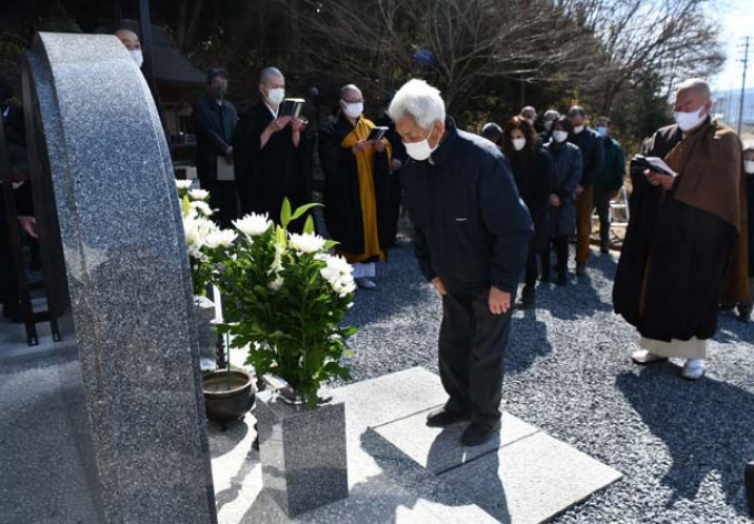 犠牲となった団員の鎮魂碑を前に供養法要を営む参列者