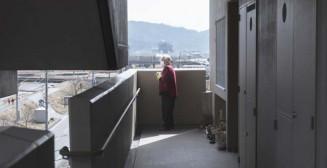 大船渡市の災害公営住宅「県営みどり町アパート」で1人暮らしをする佐藤トシさん(84)。健康のため部屋の前の通路を歩きながら、遠くに見える友人宅に向かって「おはよう、元気かい」と話しかける。声を出すと孤独のつらさが少し楽になる=5日