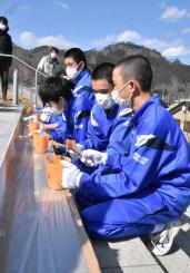 校舎に続く階段にオレンジ色の塗料を塗る釜石東中の2年生