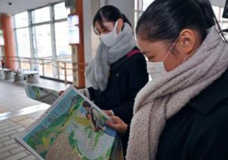JR秋田駅前で岩手日報社の号外を読む学生=11日午前7時31分
