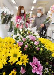 故人を思い墓前に供える花を選ぶ人たち=17日、奥州市江刺・フラワーM&Gサンエー花店