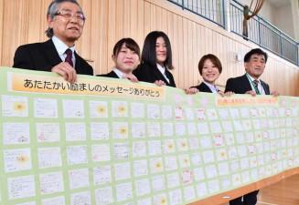 学生のメッセージを掲げる(左から)佐々木義孝教授、佐々木羽緒さん、梅原奈歩さん、石川百杜巴さんと高橋彰校長
