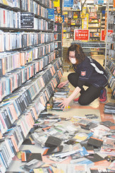 強い揺れで落下したCDを片付ける店員=20日午後6時54分、一関市千厩町・ツタヤ千厩店