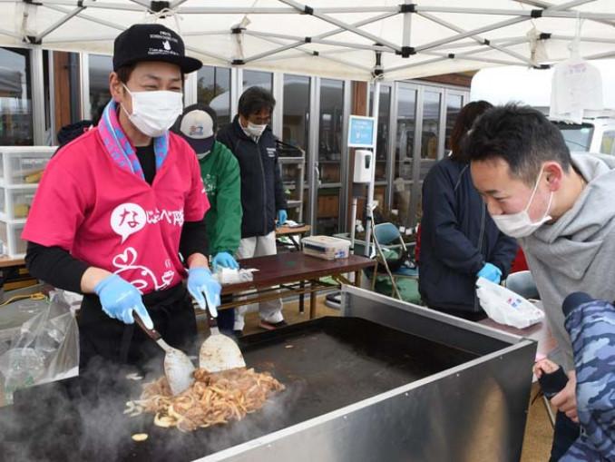 笑顔でハラミ焼を調理する星和行さん(左)