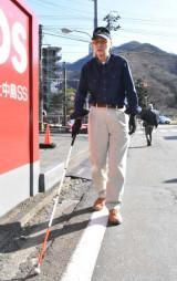 白杖を使い、白線を頼りに歩く久保秋悦さん=釜石市上中島町