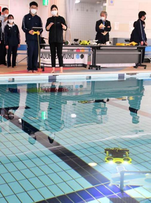 スタッフの指導を受けながら、プールの中にある水中ドローンを操縦する前沢高の生徒
