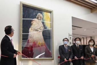 のんさんが描いた油絵「よむのむし」を除幕する関係者